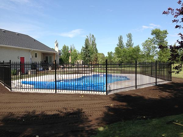 Roman pavers around pool with black ornamental fence sod