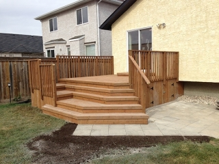 Treated brown deck with decorative angled staircase. Dynasty Wave patio in Sierra Grey.