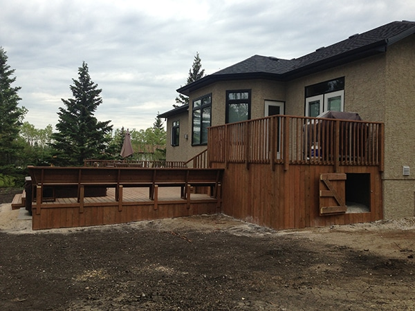 Complete yard installation. Two tier treated brown deck with built-in hot tub and storage access door, patio with fire pit and seating wall, black granite boulders, mulch, lighting, arbors