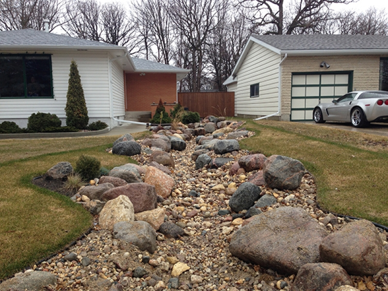 Drainage improvement from back yard decorated with round boulders