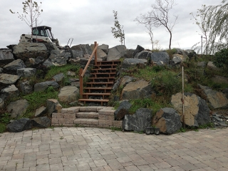 Back yard hill with built-in staircase and black granite boulders. Roman paver patio in Antique brown.