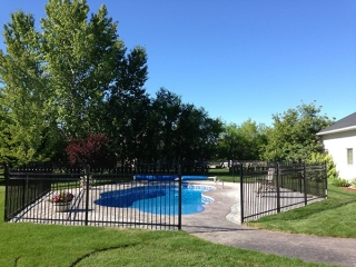 Roman pavers around pool with black ornamental fence. Sod installation.