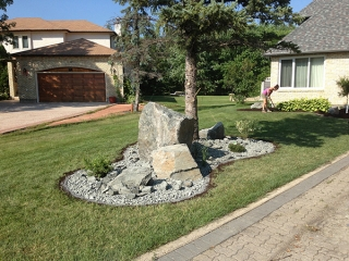 Black granite boulders and plants surrounded by one and a half inch black granite and Granite Edger.