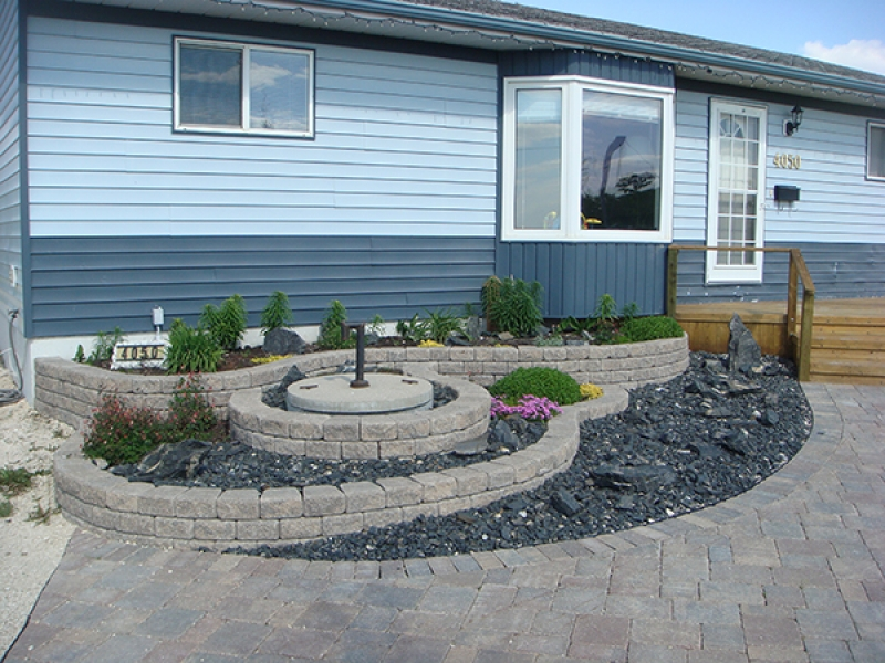 Multi-tier Roman Stack Stone planter with plants and crushed black granite. Roman paver walkway leading to treated green front deck