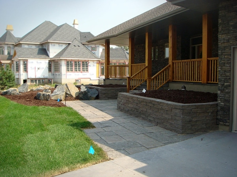 Complete yard installation. Black granite boulders, brown wood mulch, sod and trees. Patio blocks for patio, walk, and front steps. Retaining wall planters and accent lighting