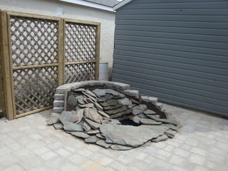 Pond and waterfall built into Roman paver patio. Treated green lattice privacy wall backdrop.