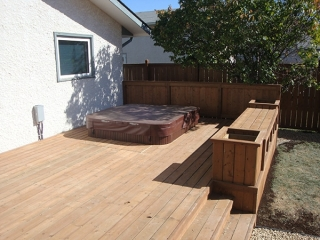 Treated brown deck with built-in hot tub, benches, and planters.