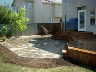 Treated brown deck with full length staircase leading to partially wet Dynasty slate patio.
