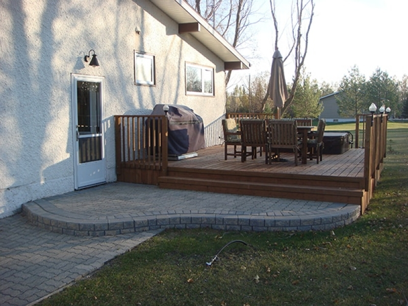 Treated brown deck with retaining wall landing and built-in hot tub.
