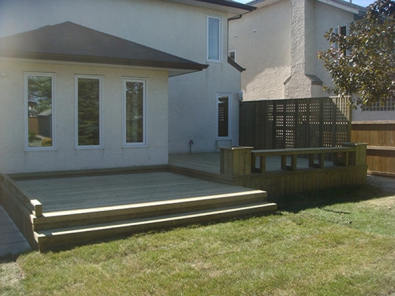 Treated green deck with built-in benches, planters, and custom lattice privacy wall. Built-in storage cupboard.
