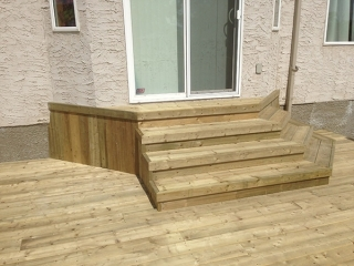 Treated green deck with decorative steps to door, Dynasty Slate patio.