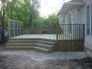 Treated green deck with wide angled stairs and lattice privacy wall.