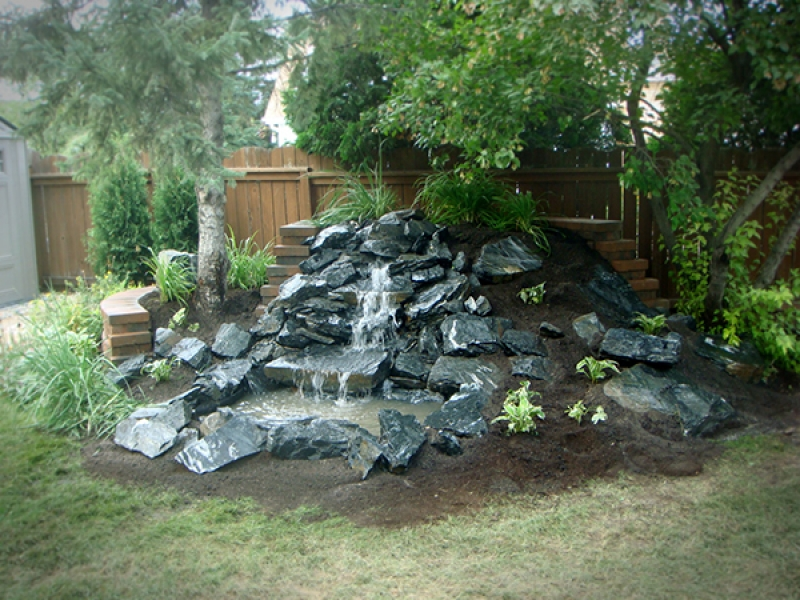 Black granite waterfall with soil and plantings. Supported from behind by a Roman Pisa retaining wall in Autumn Brown