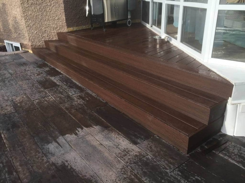 Bridgewood slab patio in cedar brown with Trex composite stairs and treated brown gazebo roof