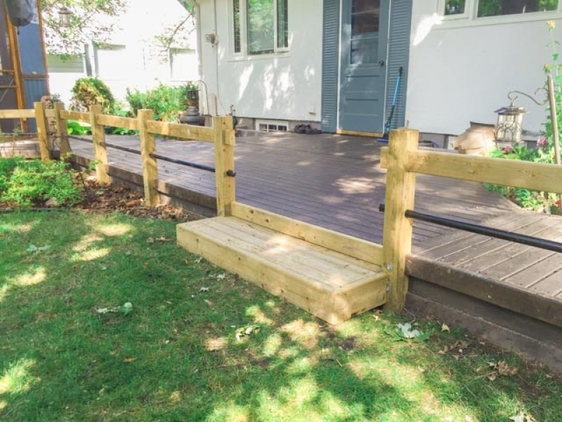 Treated green railing with black horizontal pipe