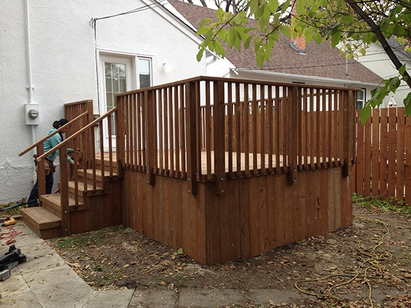 Rectangular treated brown deck with basic railing