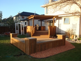 Treated brown deck with built-in cabinets, counters, benches, and pergola.
