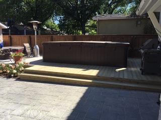 Navarro patio in Sierra Grey adjacent to treated green deck around swim spa