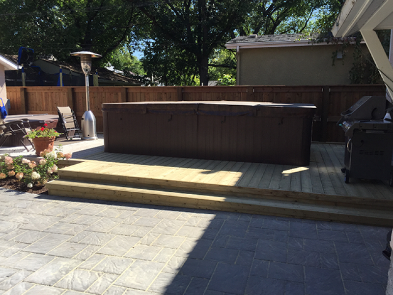 Navarro patio in Sierra Grey adjacent to treated green deck around swim spa