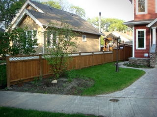 Complete yard renovation. Roman paving stones and retaining walls. Plantings and boulders surrounded by red wood mulch. Treated brown fence with white lattice top (Rock Gardens)