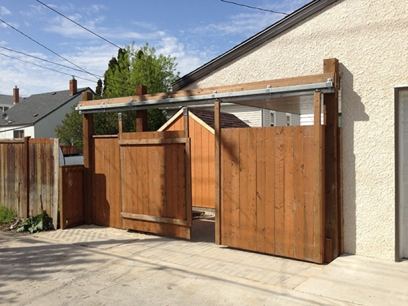 Wooden shed, fence with vehicle access gate, dual use parking pad