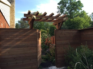 Treated brown fence with horizontal 1x6's, 6x6 posts, and gate arbor
