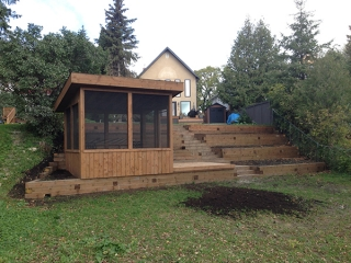 Treated brown retaining wall with built-in gazebo on bank of Assiniboine river