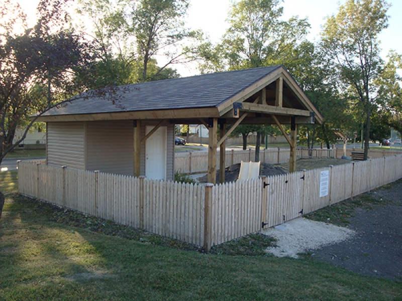 Daycare playground enclosed by cedar fence. Shelter with built-in shed, stream bed, sand box, arbor, benches, etc