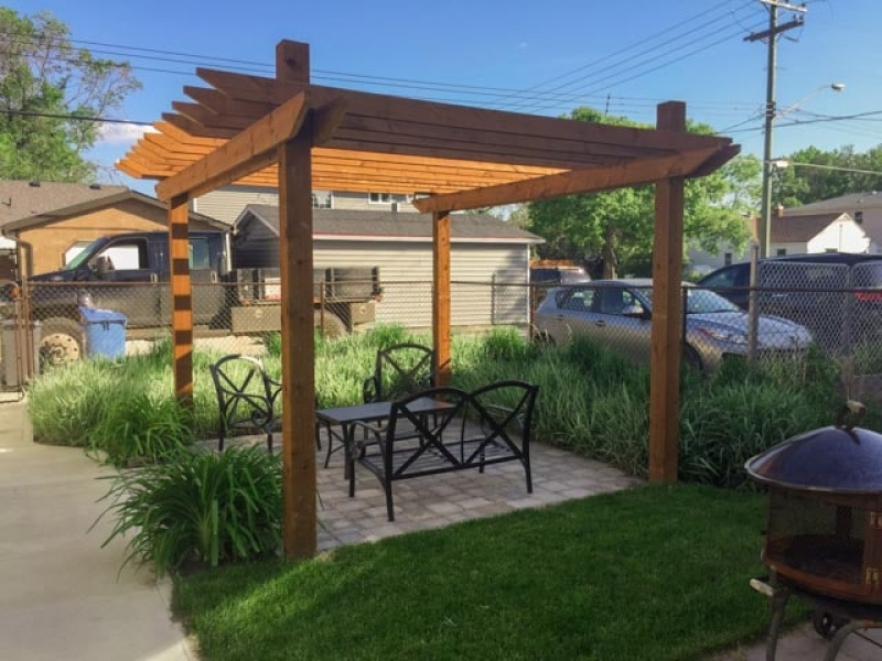 Small rear deck, arbor over paving stone patio, sod, soil, and plants
