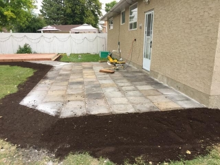 Used patio block re-installation and new ground-level deck in treated brown