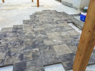 Large patio with Dynasty Slate blocks in sierra grey, posts for arbor and fence