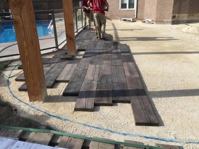 Bridgewood slab patio in cedar brown with Trex composite stairs and treated brown gazebo roof