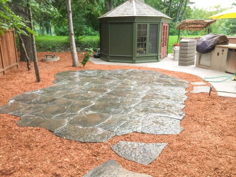 Grand Flagstone patio in Copper Canyon with orange wood mulch