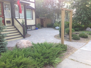 Roman paving stones covering large portion of yard. Plants and wood mulch in front