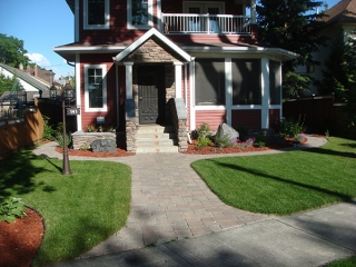 Complete yard renovation. Roman paving stones and retaining walls. Plantings and boulders surrounded by red wood mulch. Treated brown fence with white lattice top (Patios)