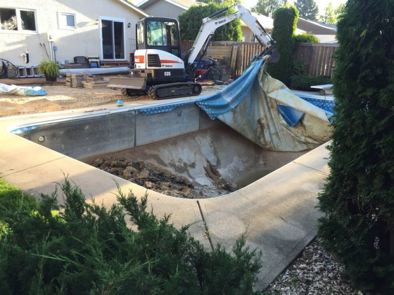 Liner and concrete being removed from in-ground pool
