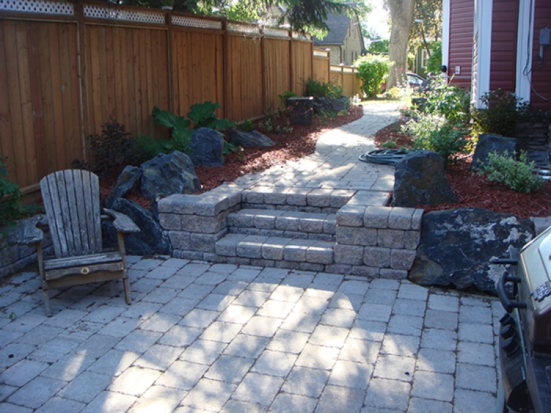 Complete yard renovation. Roman paving stones and retaining walls. Plantings and boulders surrounded by red wood mulch. Treated brown fence with white lattice top (Retaining Walls)