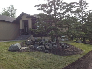 Complete yard installation. Deck, patio with fire pit and seating wall, black granite boulders, mulch, lighting,arbors