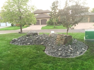 Front yard re-done with plants and black granite boulders