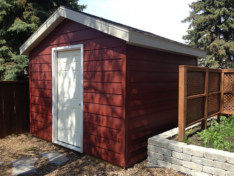 Natural wood mulch, sod, shed with Canexel siding, composite deck, Roman Paving Stones and Retaining Walls, Treated Brown Fencing.