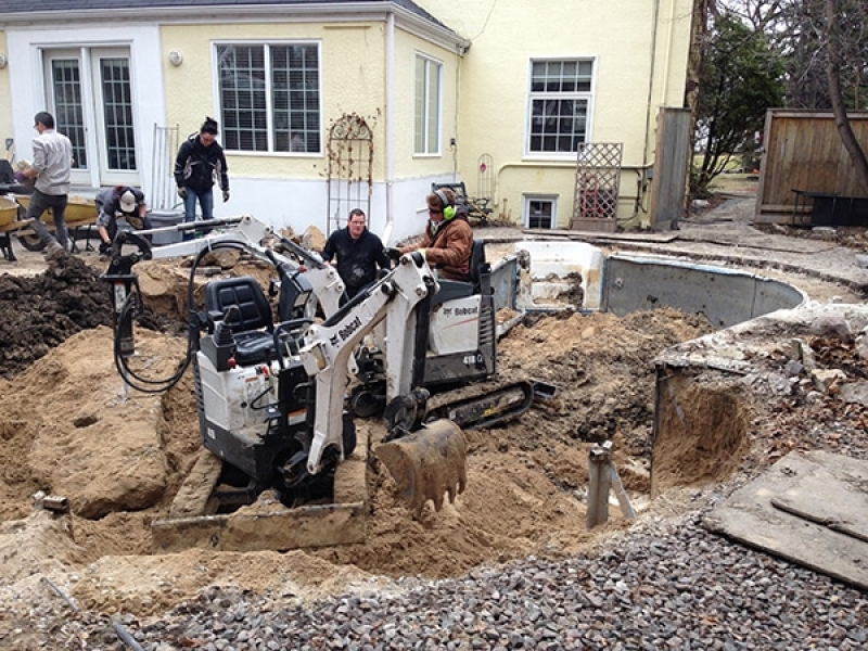 Swimming pool removal with mini excavators and wheelbarrows