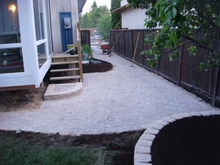 Holland paving stone patio. Roman Stack Stone retaining wall planters filled with soil.
