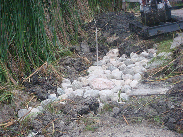 Boulders being installed to reduce erosion by man-made lake (rock gardens, grading and drainage).jpg