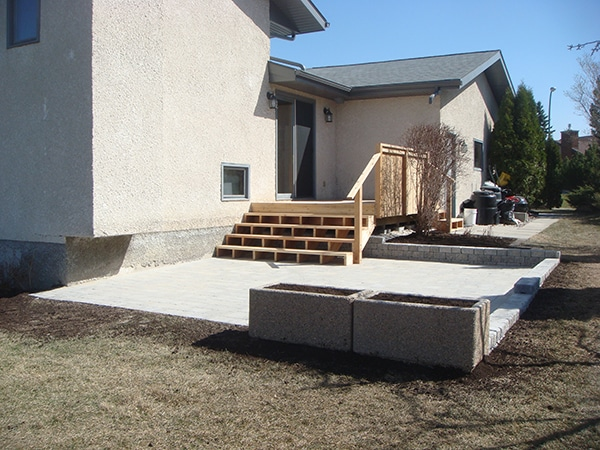 Cedar deck leading to Roman paver patio. Roman stack stone retaining wall and pebblestone planters.