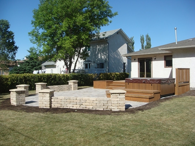 Treated brown deck with built-in hot tub and planters. Wide staircase leading onto Roman paver patio with Quarry Stone pillars and seating walls.