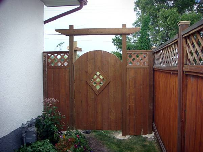Decorative treated brown gate and adjacent sections added to existing fence (fences)