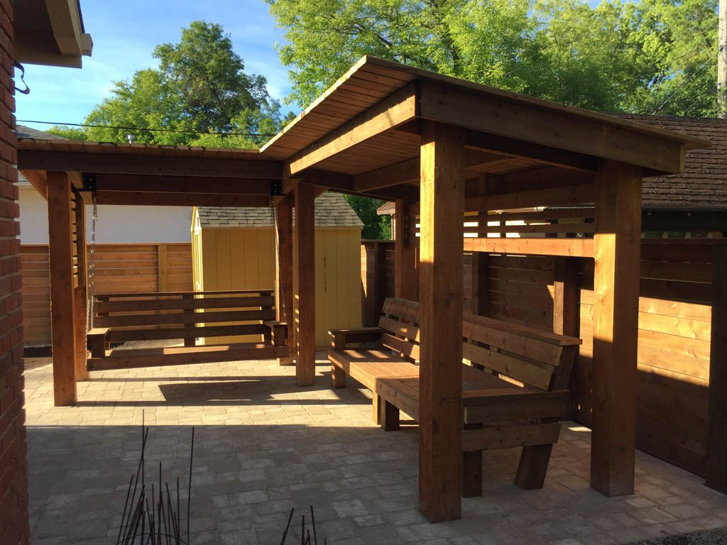 Treated brown pergola with hanging bench, fixed bench, Roman paving stones, planter with trellis, etc