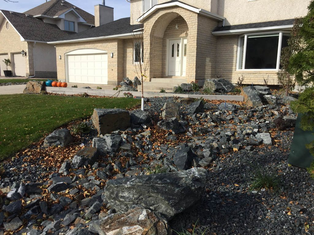 Front yard renovation with Architextures retaining wall, black granite, plants, sod