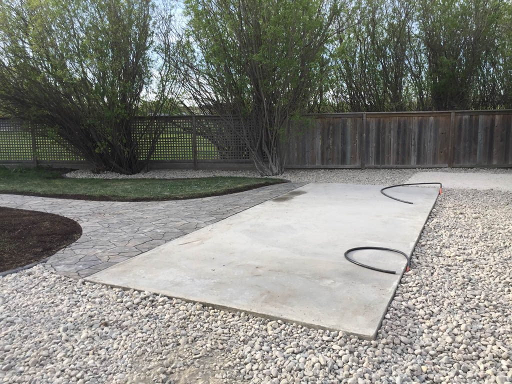 Swim spa pad, large window wells, re-grading, flagstone pathway, and decorative stone