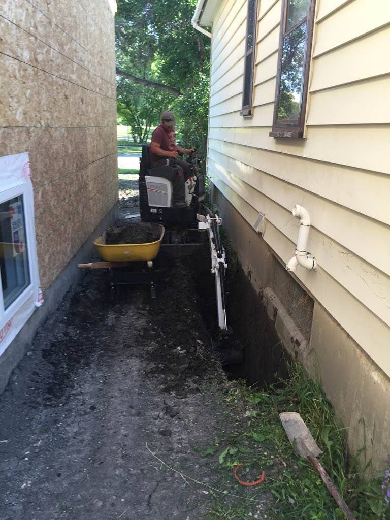 Mini excavator digging for foundation repair (Bobcat + excavator service)